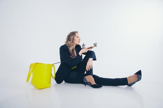 Praca w biurze, biznes plan, moda - szczęśliwa bizneswoman w czarno-żółtym garniturze uśmiechająca się do telefonu. śliczna kobieta