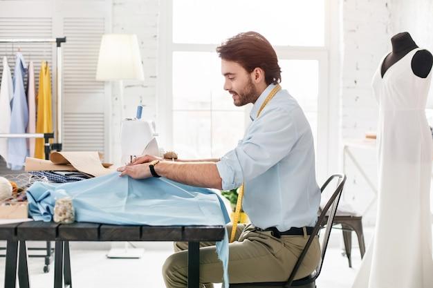 Praca w biurze. poważny, doświadczony krawiec uśmiechnięty i pracujący na maszynie do szycia