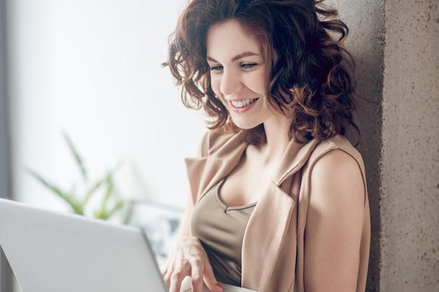 Praca w domu. ciemnowłosa ładna kobieta pracuje na laptopie i wygląda na skoncentrowaną