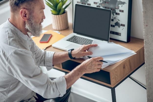 Praca w domu. dojrzały biznesmen pracujący w domu i przyglądający się dokumentom