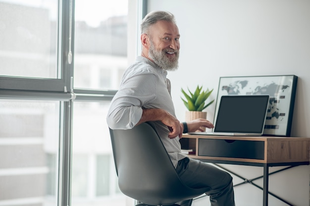 Praca w domu. dojrzały mężczyzna w białej koszulce pracujący na laptopie