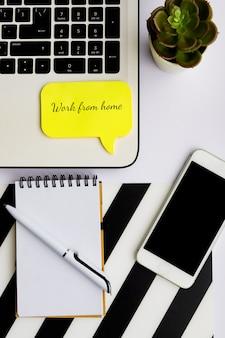 Praca w domu. izolacja społeczna podczas pandemii koronawirusa. widok z góry domowego biura w czerni i bieli z laptopem, smartfonem i notatnikiem z piórem.