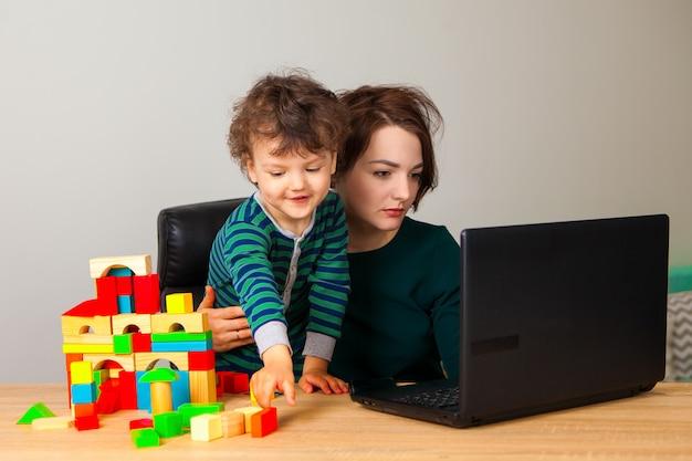 Praca w domu. kobieta siedzi przy laptopie, a dziecko bawi się w kostki i buduje duży, wielopiętrowy dom.