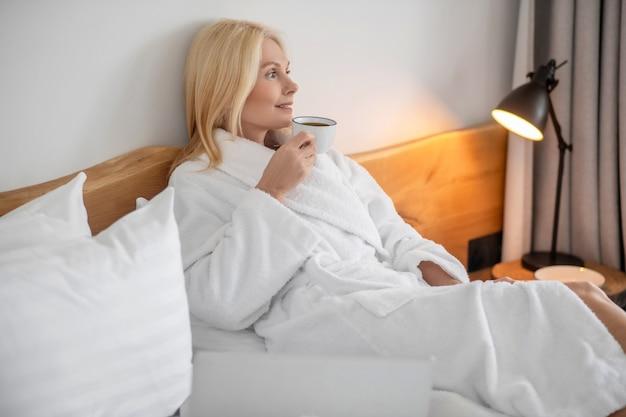Praca w domu. ładna blondynka pracuje w domu i czuje się komfortowo
