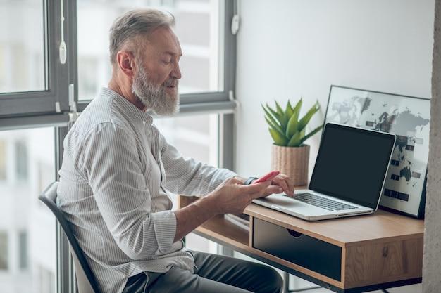 Praca w domu. mężczyzna w białej koszulce ze smartfonem w rękach pracuje w domu