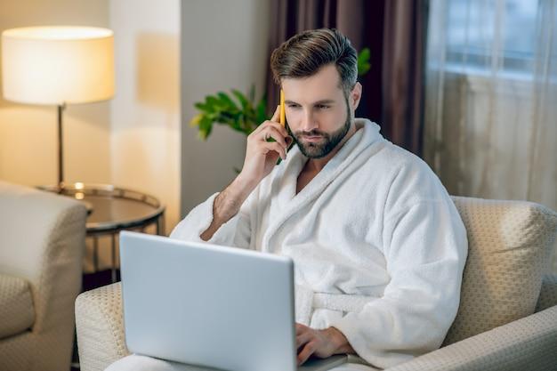 Praca w domu. młody brodaty mężczyzna w białym szlafroku pracuje na laptopie i rozmawia przez telefon