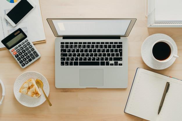 Praca w domu, nauka online. drewniane biurko, stół. widok z góry. kształcenie na odległość. jedzenie z pracą.