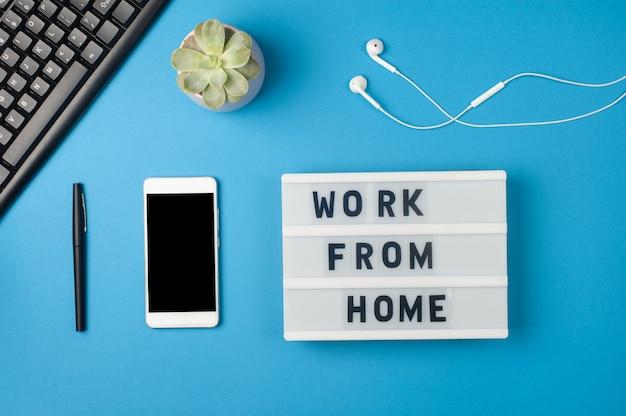 Praca w domu - tekst na wyświetlaczu lightbox i makieta smartfona na niebieskim tle w miejscu pracy. czarna klawiatura i białe słuchawki. koncepcja pracy niezależnej
