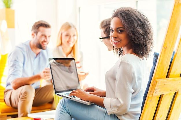 Praca w kreatywnym środowisku. uśmiechnięta młoda afrykanka pracująca na laptopie, podczas gdy jej koledzy dyskutują o czymś w tle