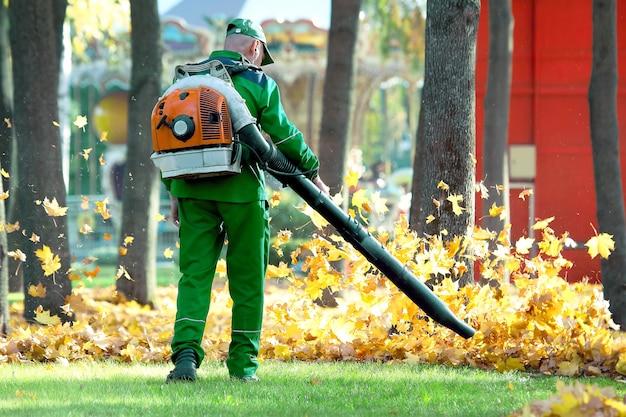 Praca w parku usuwa jesienne liście za pomocą dmuchawy. pracownicy socjalni służb miejskich