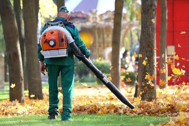 Praca w parku usuwa jesienne liście za pomocą dmuchawy