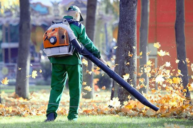 Praca w parku usuwa liście za pomocą dmuchawy. pracownicy socjalni służb miejskich