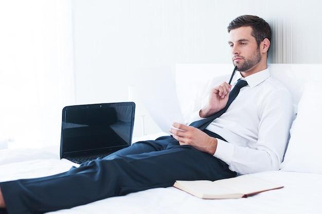 Praca w pokoju hotelowym. rozważny młody człowiek w koszuli i krawacie bada dokument leżąc w łóżku w pokoju hotelowym