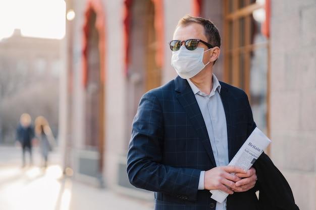 Praca w sytuacji pandemicznej. pracownik firmy lub przedsiębiorca nosi maskę medyczną w celu ochrony przed koronawirusem