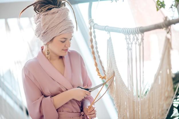Praca w toku. kobieta w nakryciu głowy do cięcia przędzy podczas tkania makramy