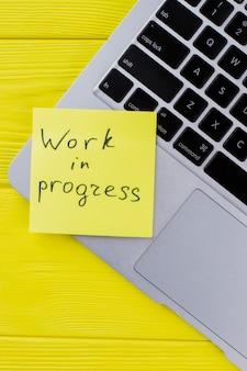 Praca w toku koncepcji. klawiatura laptopa na żółtym drewnie. widok z góry na płasko.