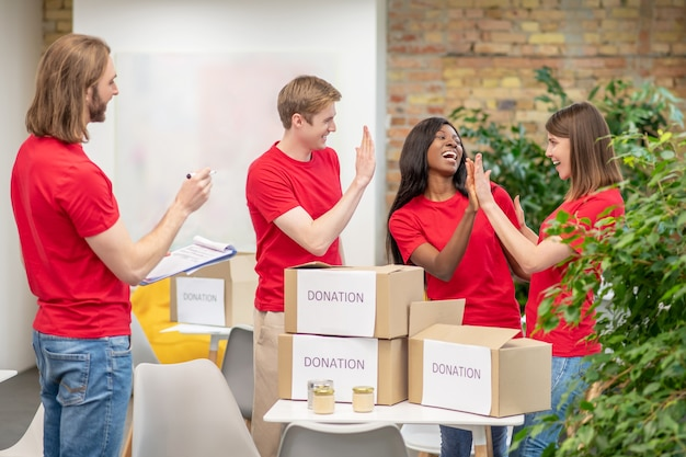 Praca w zespole. młodzi radośni wolontariusze w czerwonych koszulkach pracujący na terenie ośrodka charytatywnego pakujący pudełka na datki