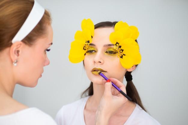 Praca wizażysty. piękno portret brunetka z długimi rzęsami w postaci tulipanu. oko z bliska