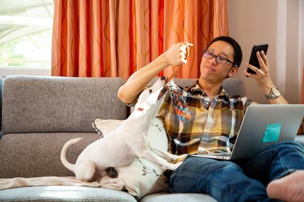 Praca z domu. azjaci pracując i sprawdzając dokument z laptopem i bawić się z psem w biurze.