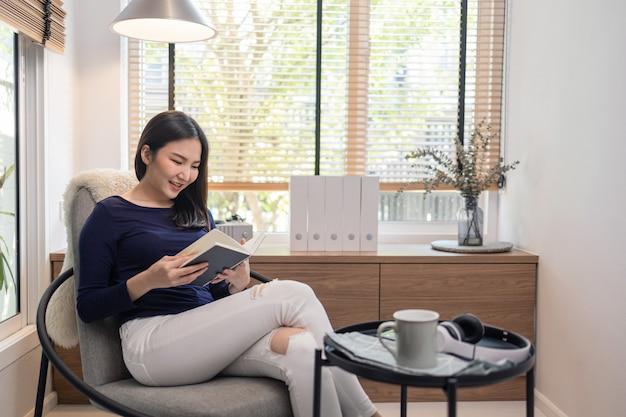 Praca z domu koncepcja ładnej kobiety siedzącej na nowoczesnym krześle w ładnie urządzonym minimalistycznym pokoju i czytającej słynną książkę.