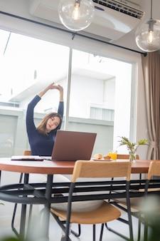 Praca z domu koncepcja przedsiębiorczyni jest zrelaksowana, rozciągając ramiona podczas pracy