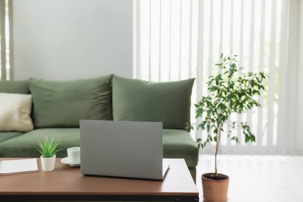 Praca z domu, obszar roboczy, pulpit, koncepcja pracy zdalnej, szary cienki laptop na brązowym drewnianym stole z białą filiżanką kawy, zielona sofa, doniczka, notatnik. stylowe apartamenty strefa komfortu