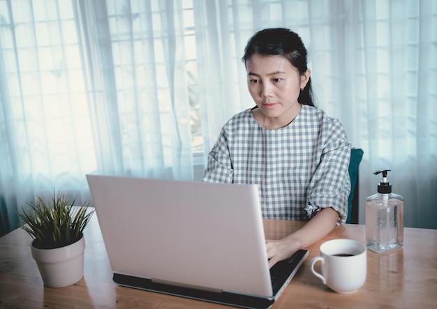 Praca z domu społecznej odległości koncepcji. kobiety pracujące i poddane kwarantannie w domu. stół do pracy z komputerem i alkoholowym żelem do ręcznego wcierania