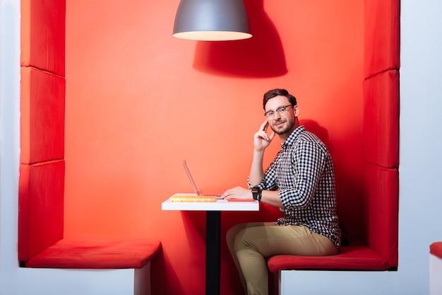 Praca z komfortem. młody nauczyciel akademicki mający produktywny dzień w wygodnym czerwonym miejscu pracy i uśmiechnięty, siedząc ze swoim laptopem