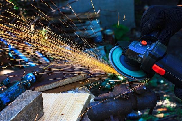 Praca z metalowym ślusarzem szlifierką praca z iskrami