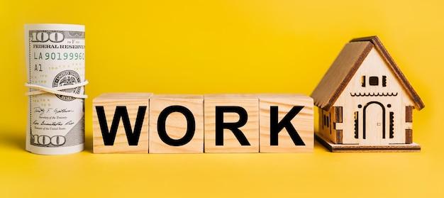 Praca z miniaturowym modelem domu i pieniędzmi na żółtym tle. pojęcie biznesu, finansów, kredytu, podatków, nieruchomości, domu, mieszkania