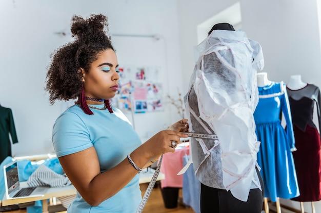 Praca z modelem. skoncentrowany młody projektant mierzący linię talii z linijką zbierającą wymiary do przyszłego stroju