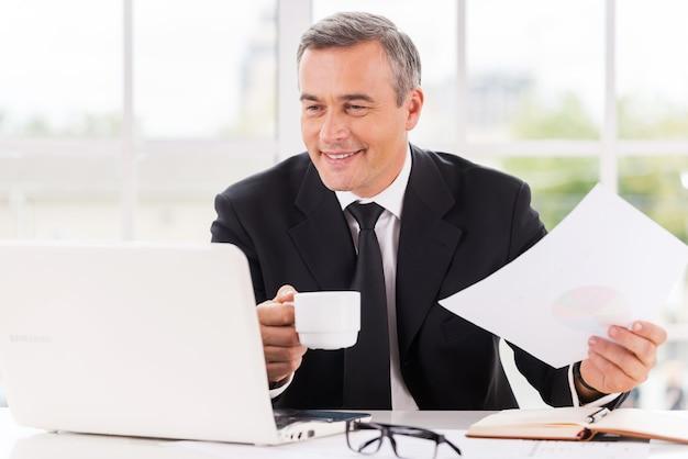 Praca z przyjemnością. szczęśliwy dojrzały mężczyzna w stroju formalnym pracujący i pijący kawę siedząc w swoim miejscu pracy