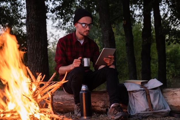 Praca z technologią w niekonwencjonalnej koncepcji miejsca. mężczyzna zdalnie pracujący z komputerem typu tablet podczas pieszej wycieczki obok ogniska na kempingu.