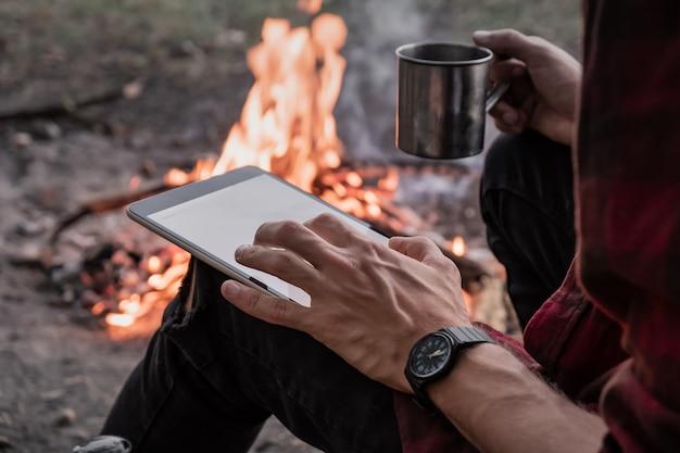 Praca z technologią w niekonwencjonalnej koncepcji miejsca. używanie tabletu do pracy zdalnej podczas pieszej wycieczki obok ogniska na kempingu.