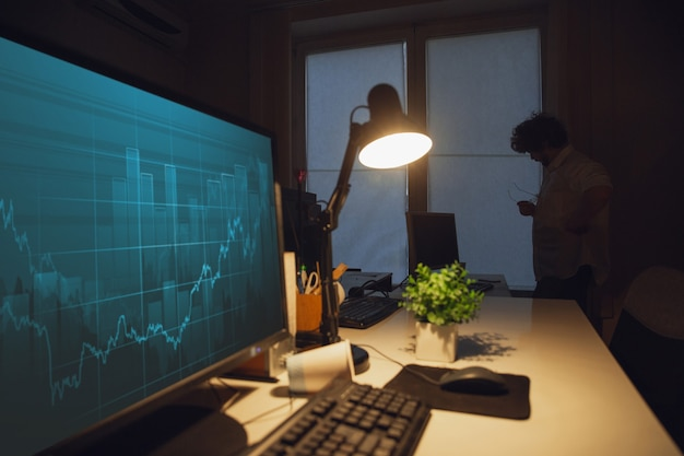 Praca z wykresami. mężczyzna pracujący w biurze, przebywający do późnej nocy.