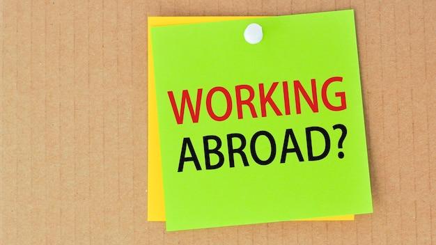 Praca za granicą napisana na zielonym papierze i przypięta na tablicy korkowej