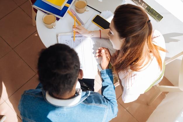 Praca zbiorowa. uważny brunetka mężczyzna słuchający swojego przyjaciela podczas wykonywania zadania