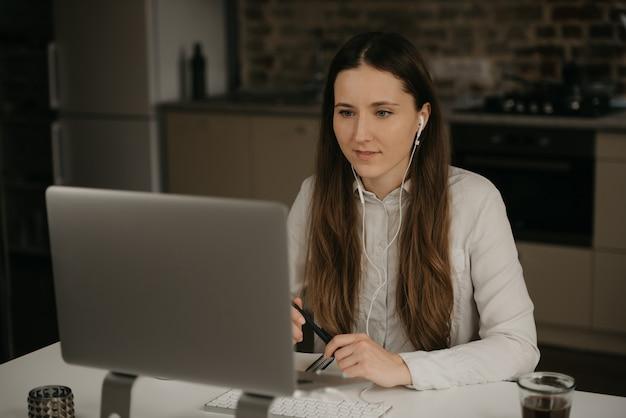 Praca zdalna. kaukaska brunetki kobieta z hełmofonami pracuje zdalnie na jej laptopie. dziewczyna w białej koszuli rozmawia wideo ze swoimi partnerami biznesowymi w swoim domowym miejscu pracy.