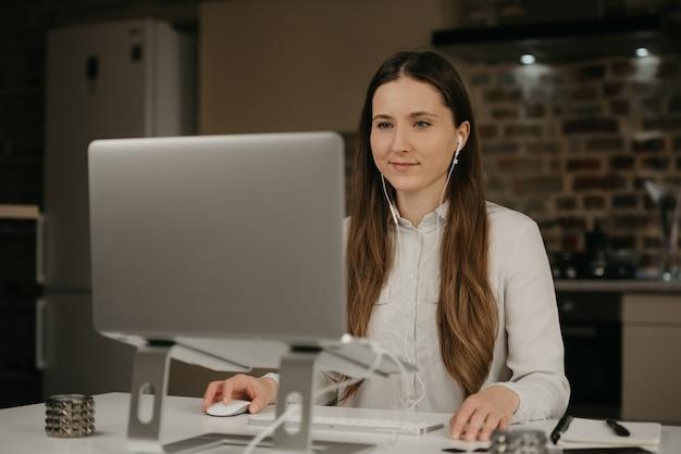 Praca zdalna. kaukaska kobieta ze słuchawkami pracującymi zdalnie na swoim laptopie. bizneswoman w białej koszula robi biznesowi przy jej domowym miejscem pracy.