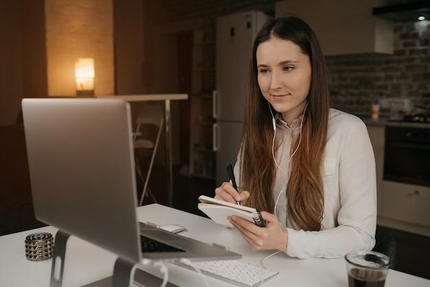 Praca zdalna. kaukaska kobieta ze słuchawkami pracującymi zdalnie na swoim laptopie. dziewczyna w białej koszuli robi notatki podczas odprawy biznesowej online w swoim przytulnym domowym miejscu pracy.