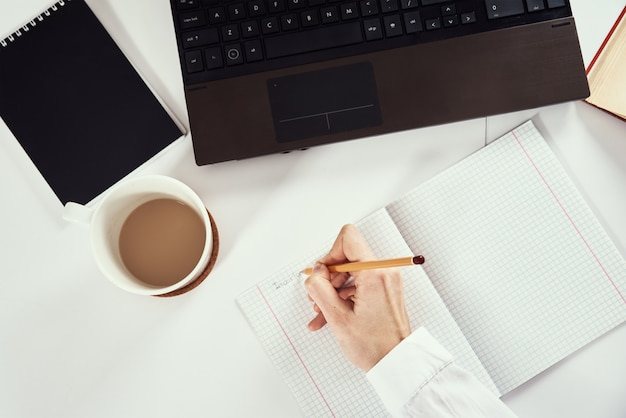 Praca zdalna. kobieta robi notatki w notatniku i za pomocą laptopa do nauki. kształcenie na odległość i koncepcja e-learningu