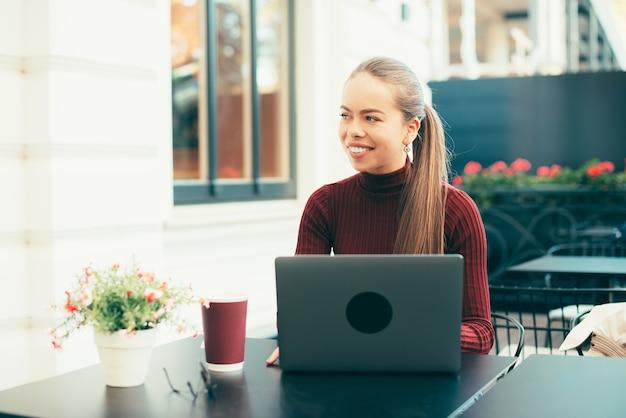 Praca zdalna, kobieta siedzi w kawiarni na świeżym powietrzu i pracuje na laptopie