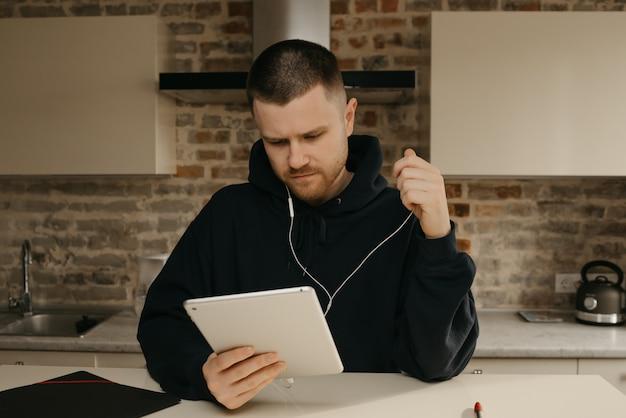 Praca zdalna. mężczyzna z brodą pracujący zdalnie na tablecie.