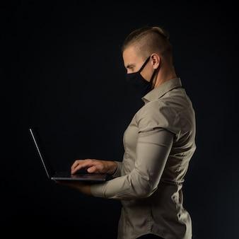 Praca zdalna. mężczyzna z laptopem nad czerni ścianą