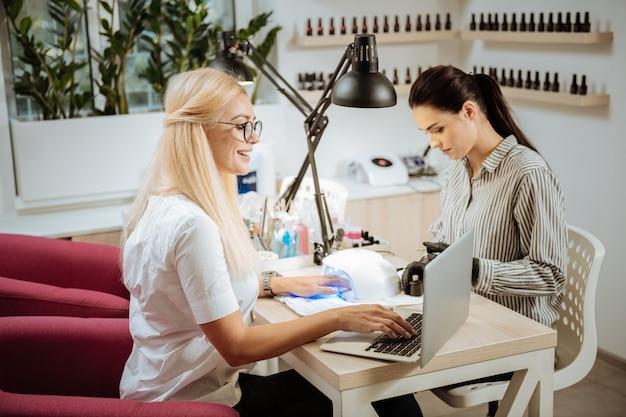 Praca zdalna. przyjemna piękna blondynka w okularach pracuje zdalnie w salonie piękności