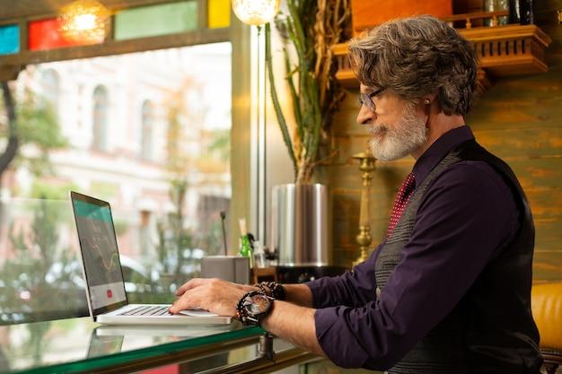 Praca zdalna. skoncentrowany brodaty mężczyzna siedzący przy stoliku w kawiarni z laptopem pracuje nad swoim nowym projektem.
