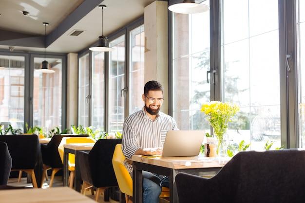 Praca zdalna. wesoły szczęśliwy człowiek siedzący przy laptopie podczas pracy w kawiarni