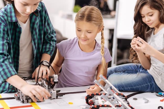 Praca ze szczegółami. pracowite zachwycone uważne dzieciaki siedzące w laboratorium robotyki i naprawiające cyber-urządzenia podczas lekcji przedmiotów ścisłych