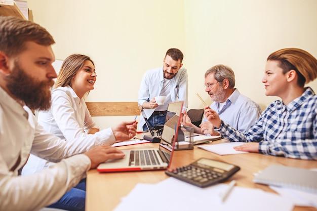 Praca zespołowa. fotografuje młodych businessmans pracujących z nowym projektem w biurze