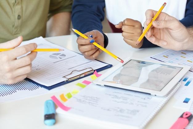 Praca zespołowa. grupa ekspertów marketingowych pracujących razem nad projektem startowym, siedząc przy stole z kartkami papieru i tabletem cyfrowym.